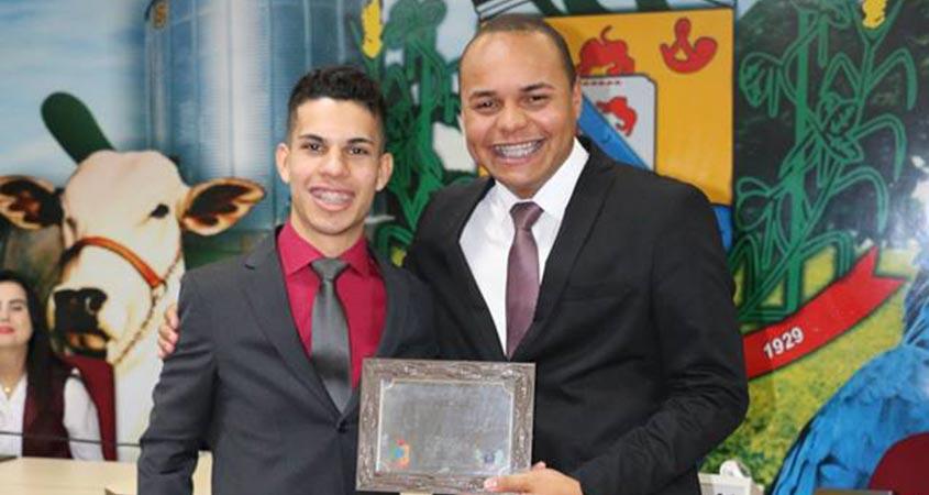 Fernando Bononi, Presidente da Câmara Jovem de Rio Brilhante, à esquerda, homenageia o Jovem Senador Carlos Henrique