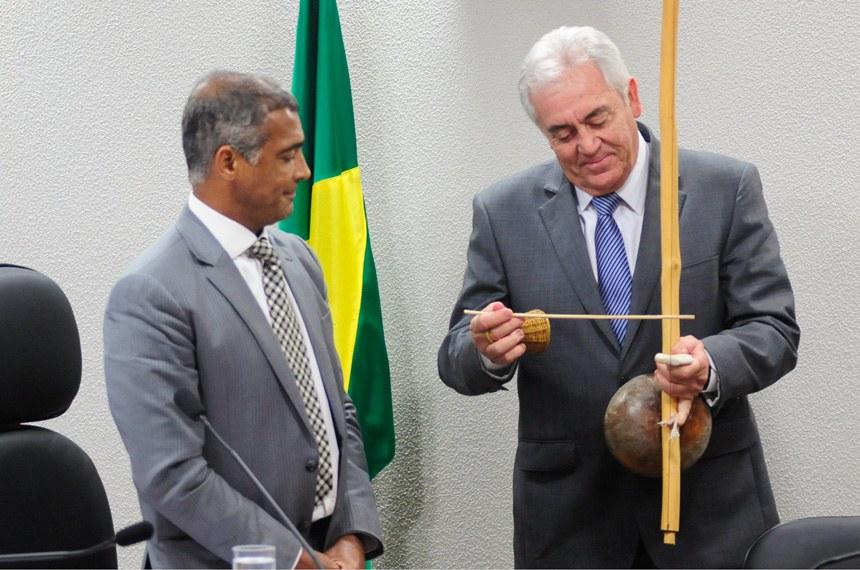 Otto Alencar, que relatou a proposta, executa toque no berimbau observado pelo presidente da CE, Romário