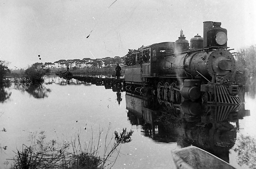 Trem carregado de toras enfrenta enchente do Rio Negro, em Três Barras (SC)