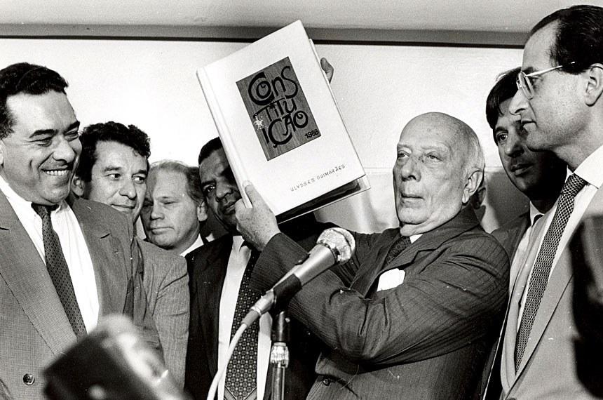Cercado de parlamentares, o deputado Ulysses Guimarães (1916-1992) ergue a Constituição de 1988.