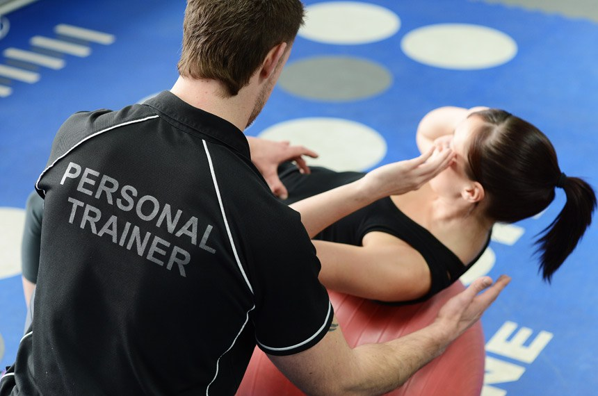 Personal trainer helping young woman in gym with crunching exercises.  Personal trainer auxiliando aluno na execução de atividade física