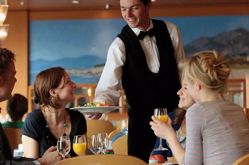 Senai oferece curso gratuito de garçom. Garçom serve mesa em restaurante.