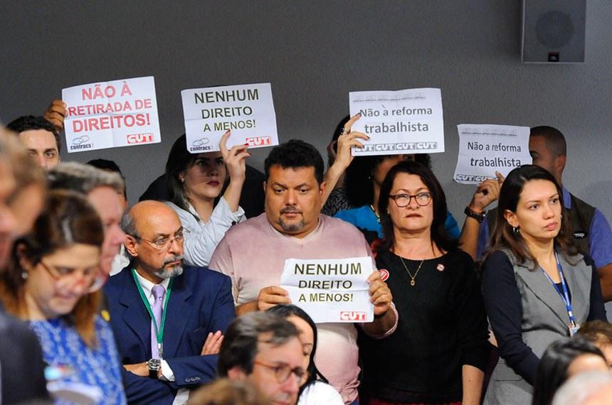 Comissão de Assuntos Econômicos (CAE) realiza audiência pública interativa para debater a reforma trabalhista.   Manifestantes á bancada exibem cartazes durante a CAE.   Foto: Pedro França/Agência Senado