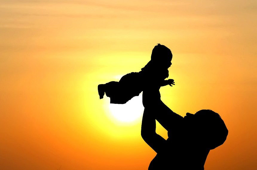 Sombra, silhueta, de homem levantando bebê. Ao fundo pôr do sol na praia.