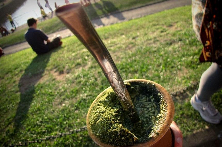 Mão segurando copo de chimarrão.