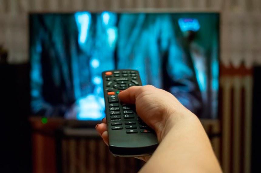 Pessoa, mulher, assiste TV. (TV, TV a cabo, TV paga, canais pagos, controle remoto)  Imagem em baixa resolução