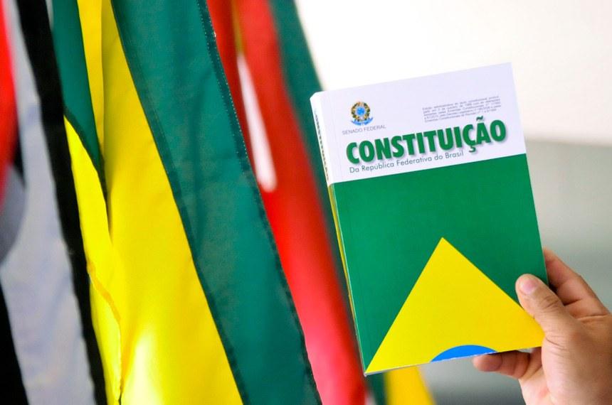 Detalhe de mão segurando a Constituição Federal junto às bandeiras dos Estados Federativos do Brasil. O STF determinou que o Legislativo faça uma nova lei de repartição do Fundo de participação dos Estados.