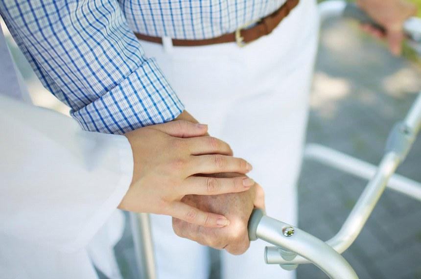 Idoso recebe ajuda e cuidados ao caminhar com andador.