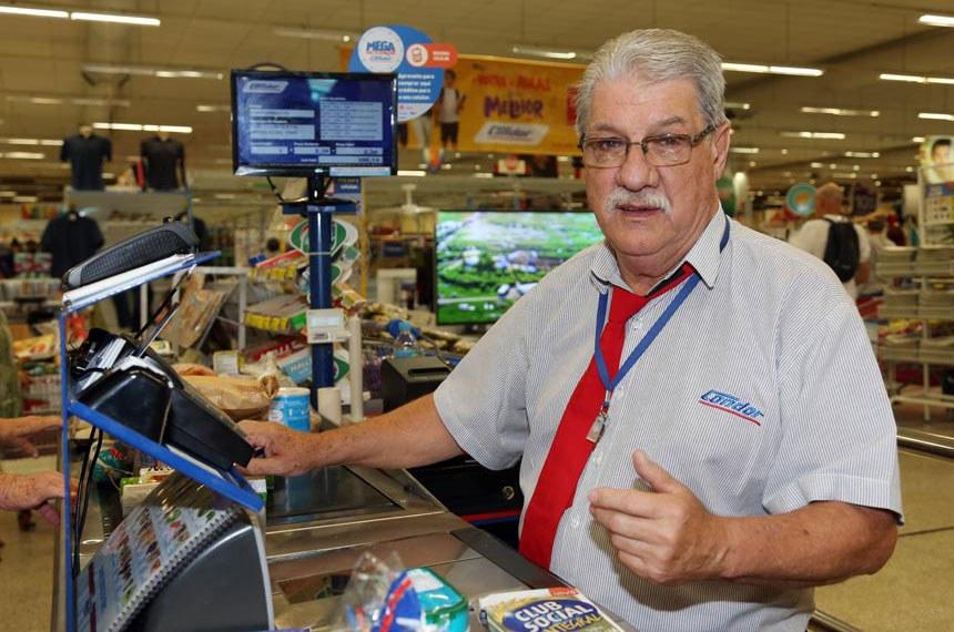 Aposentado Marcos Henrique Ribeiro trabalha como caixa de supermercado em Curitiba.  Agência do Trabalhador - Rendimento dos idosos do Paraná tem maior expansão do Sul e Sudeste.