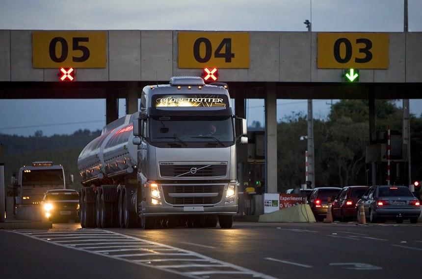 Caminhão e carros de passeio passam por pedágio em rodovia brasileira