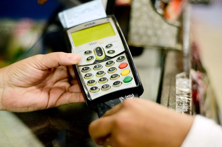 Compras com cartão de crédito - Cliente passa cartão em máquina de crédito na Feira dos Importados em Brasília.