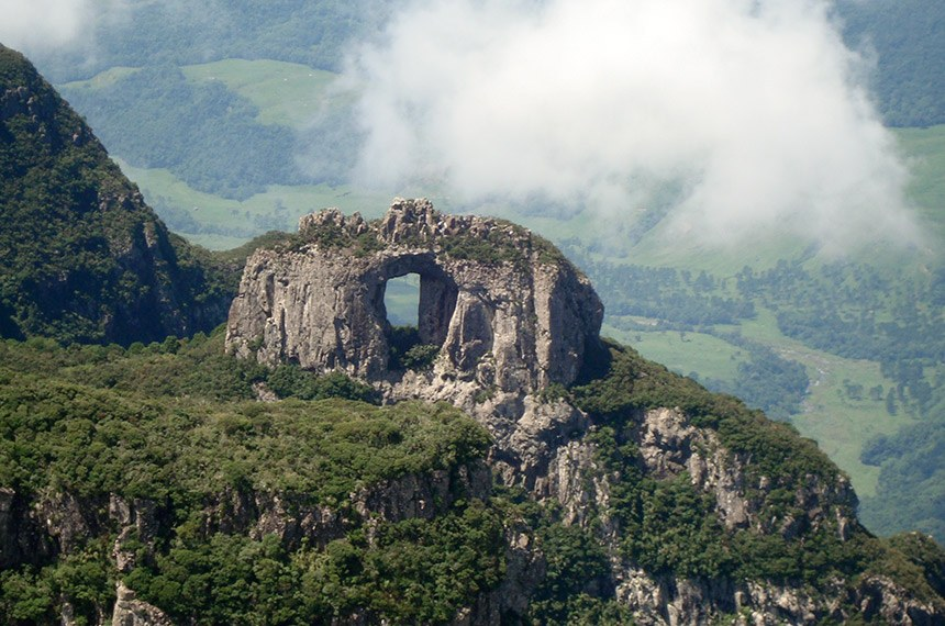 Parque Nacional de  São Joaquim  Do mirante do Morro da Igreja, se avista a Pedra Furada (foto abaixo), um portal rochoso em forma de janela, medindo cerca de 30 metros de largura, esculpida pela natureza em meio à Mata Atlântica.