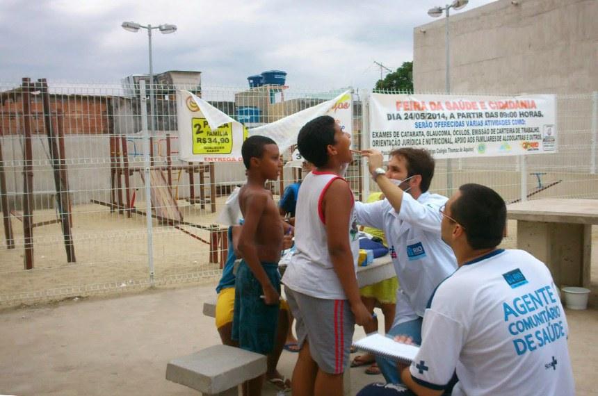 Na foto Dr. Érico Souza (Dentista da CFSVM) e o Agente Comunitário de Saúde Lauro Baptista atendendo as crianças da Comunidade do Morro da Coroa, Rio de Janeiro-RJ.