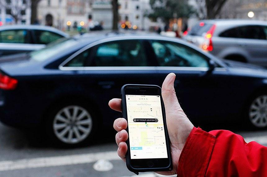 Aplicativo de UBER é mostrado na tela do celular enquanto os carros dirigem perto em Washington, CC.