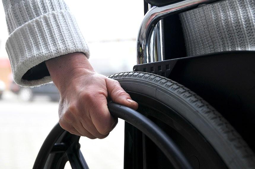 Pessoa se locomove em cadeira de rodas.