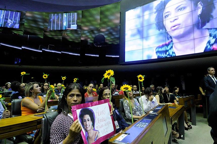 """Plenário da Câmara dos Deputados durante sessão não deliberativa solene em homenagem à vereadora Marielle Franco (PSOL-RJ) e seu motorista, Anderson Gomes, assassinados no Rio de Janeiro.  Segurando girassóis, parlamentares do PSOL, PT, PSB e militantes dos direitos humanos marcharam desde a taquigrafia até o plenário da Câmara, onde acompanharam a sessão solene no plenário.  Uma grande faixa preta com os dizeres """"Marielle, presente! Anderson, presente! Transformar luto em luta!"""" foi estendida em frente a mesa de trabalhos.  Painel eletrônico exibe vídeo com o depoimento de Marielle.  À bancada, mulher segura cartaz: """"Acarí chora mais uma vez"""".  Foto: Geraldo Magela/Agência Senado"""