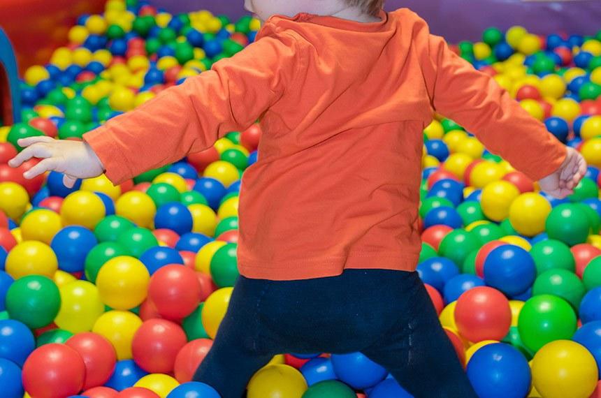 Criança, garoto, brinca em piscina de bolinhas de shopping