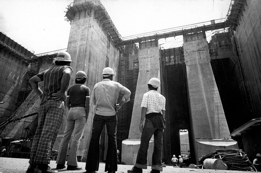 Operários olham a barragem da Usina de Itaipu sendo erguida: período de obras grandiosas e pouca transparência.