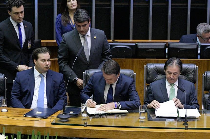 Entre Rodrigo Maia e Eunício Oliveira, Jair Bolsonaro assina o termo de posse