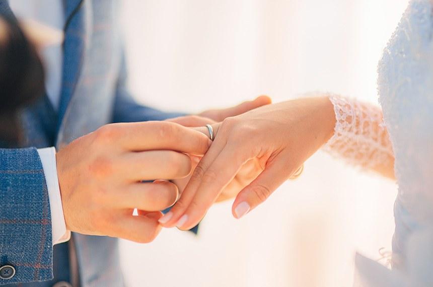 The newlyweds exchange rings   -----------  Os recém-casados trocam alianças no casamento