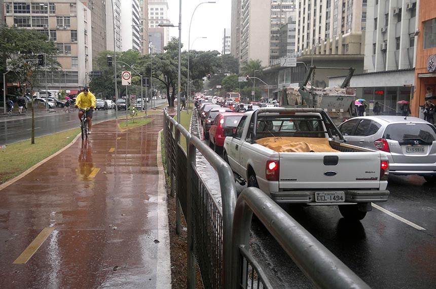 Ciclista na ciclovia da Rua Faria Lima, São Paulo - SP, em dia de chuva.