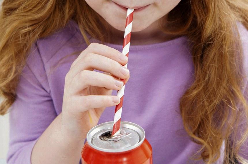 BIE  - Criança bebe refrigerante em lata com canudinho.  Foto: Getty Images/iStockphoto