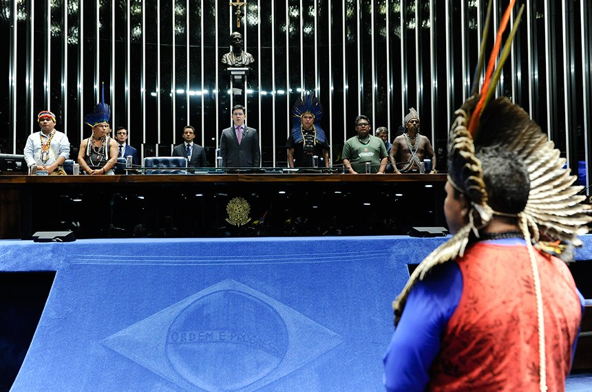 Plenário do Senado Federal durante sessão especial destinada a homenagear os povos indígenas.   Em posição de respeito, convidados e parlamentares acompanham execução do Hino Nacional Brasileiro.    Mesa: conselheiro da Coordenação das Organizações Indígenas da Bacia Amazônia, Tuntiak Katan; representante da Atiguaçu da Região Centro-Oeste, Eliseu Pereira Lopes; presidente da sessão, senador Randolfe Rodrigues (Rede-AP); representante da Articulação dos Povos Indígenas do Brasil, vereador em Sidrolândia (MS), Otacir Terena; representante da Coordenação das Organizações da Amazônia Brasileira, Toya Manchineri; cacique Xucuru, Marcos Xucuru.  Foto: Jane de Araújo/Agência Senado