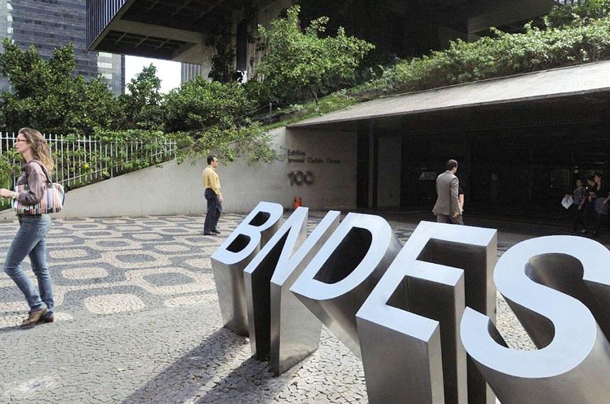Transeuntes circulam em frente à fachada do banco BNDES no Rio de Janeiro.