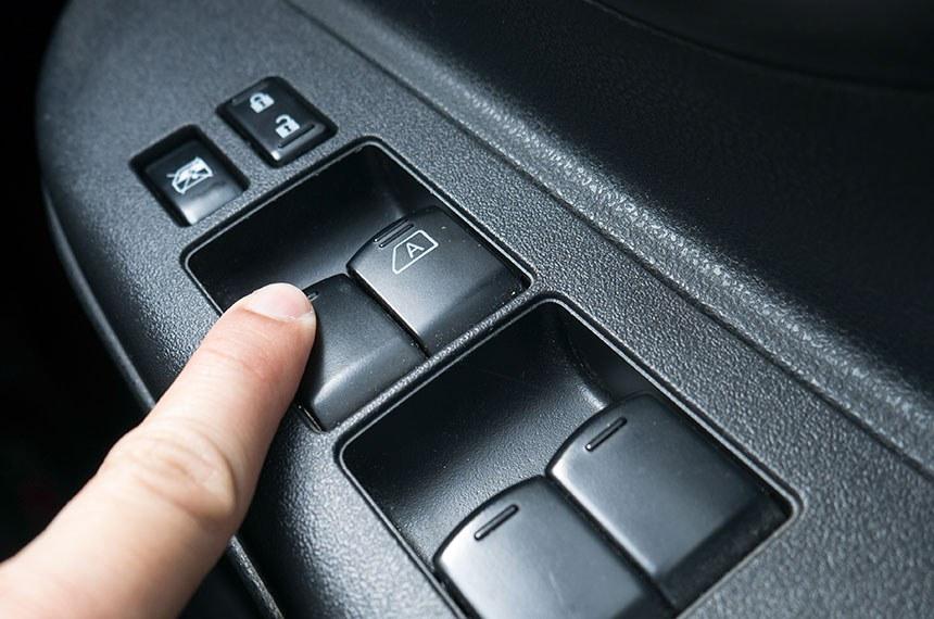 press the button to open car door . pressione o botão para abrir a porta do carro. -----------  Dedo pressiona botão automático de abertura de vidros elétricos localizado na porta, no interior de um carro.  Foto: thexfilephoto/iStockphoto