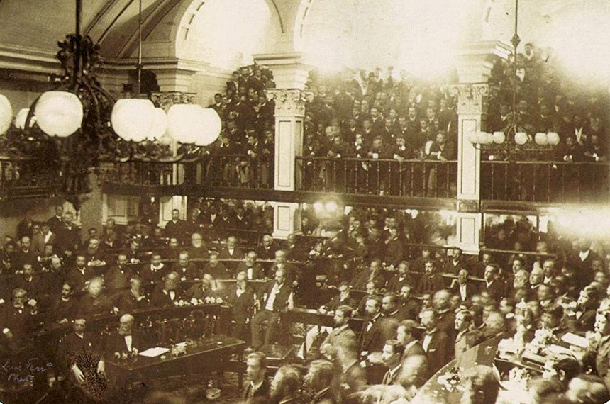 O Senado brasileiro no dia da aprovação da lei que aboliu a escravidão no país em 1888. Uma multidão está reunida assistindo no andar de cima e ao fundo no térreo.