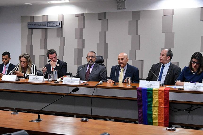 """Comissão de Direitos Humanos e Legislação Participativa (CDH) realiza audiência pública para tratar sobre: """"O Dia Internacional de Enfrentamento à LGBTIfobia"""".  Mesa: conselheiro do Conselho Nacional de Combate à Discriminação e Promoção dos Direitos de Lésbicas, Gays, Bissexuais, Travestis e Transexuais do Ministério da Mulher, da Família e dos Direitos Humanos (CNCD/LGBT/MDH), Emerson Santos; representante da Rede Trans Brasil, Tathiane Araújo; representante da Rede Nacional de Advogadas e Advogados Populares (Renap), Rodrigo Camargo; presidente da CDH, senador Paulo Paim (PT-RS); senador Confúcio Moura (MDB-RO); diretor-presidente da Aliança Nacional LGBTI+, Toni Reis; secretária da Comissão Especial da Diversidade Sexual e Gênero da Ordem dos Advogados do Brasil, Chyntia Aquino da Costa Barcellos.  Sobre a mesa, bandeira arco-íris, símbolo da comunidade LGBTQ+.  Foto: Geraldo Magela/Agência Senado"""