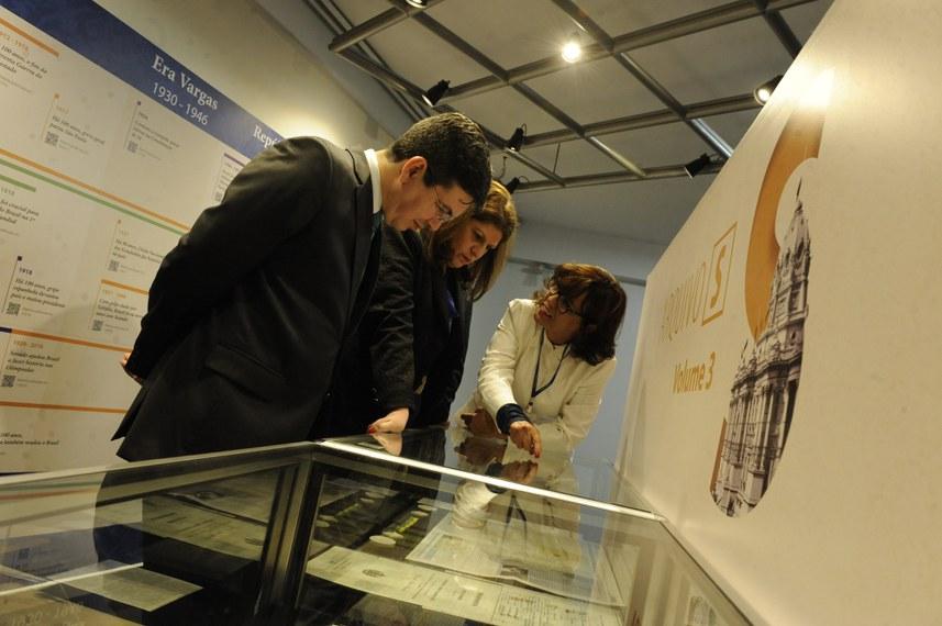 Rosa Vasconcelos (D), do Arquivo do Senado, explica detalhe da exposição a Randolfe e Ilana