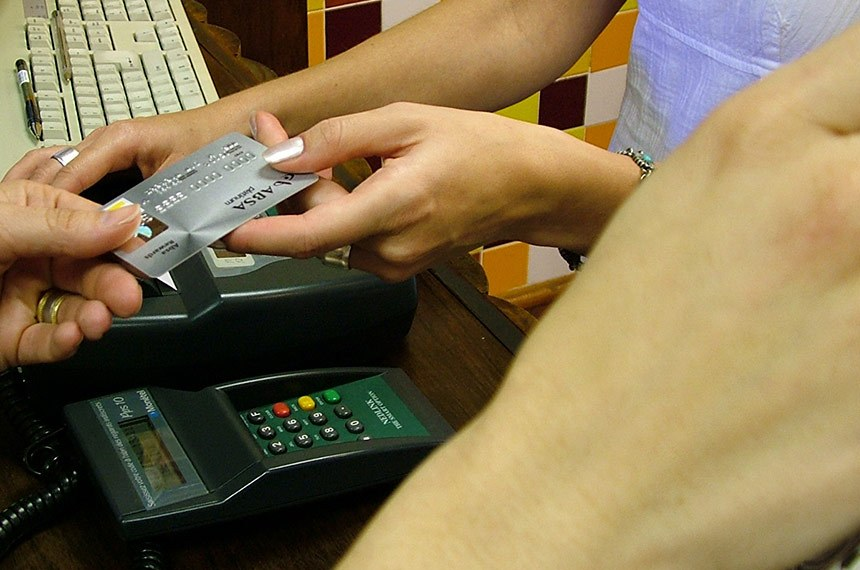 Foto: Lotus Head/stock.schng Data: 06/11/2004  Comerciante recebe cartão de crédito para pagamento de compras.
