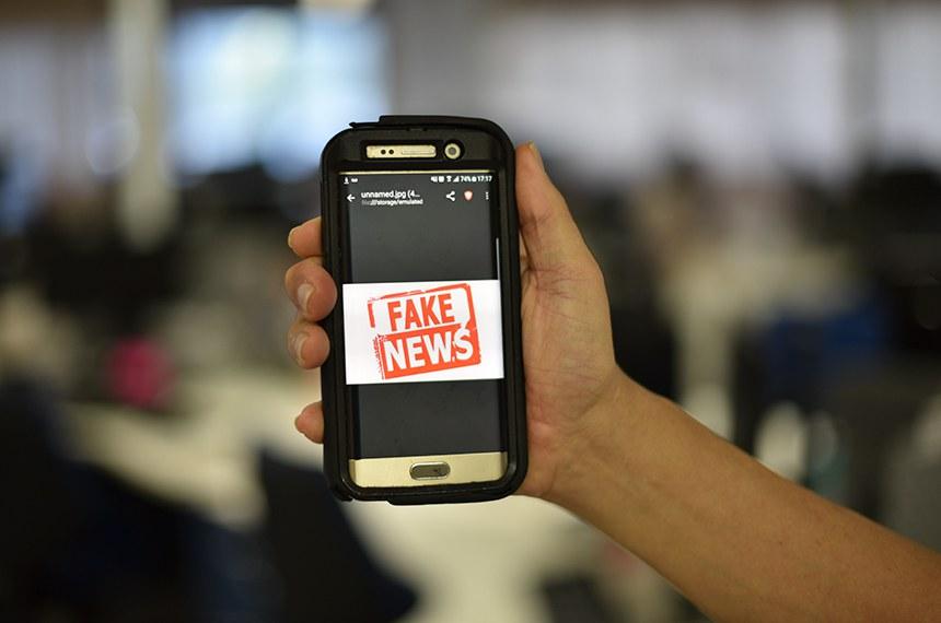 """Celular exibe imagem: """"Fake News"""".  O Plenário do Congresso Nacional derrubou, nesta quarta-feira (28), veto presidencial sobre a criminalização da divulgação de denunciações caluniosas (as chamadasfake news) com finalidade eleitoral.   A legislação brasileira avançou bastante com o Marco Civil da Internet (Lei 12.965, de 2014 ), que prevê punição para a divulgação de notícias falsas.  No Brasil, os crimes cometidos na internet são puníveis de acordo com leis que modificaram o Código Penal. É o caso da Lei 12.737, de 2012, em que invadir dispositivo com o fim de obter, adulterar ou destruir dados é um delito que pode levar a detenção de três meses a um ano e multa.  Foto: Pillar Pedreira/Agência Senado"""