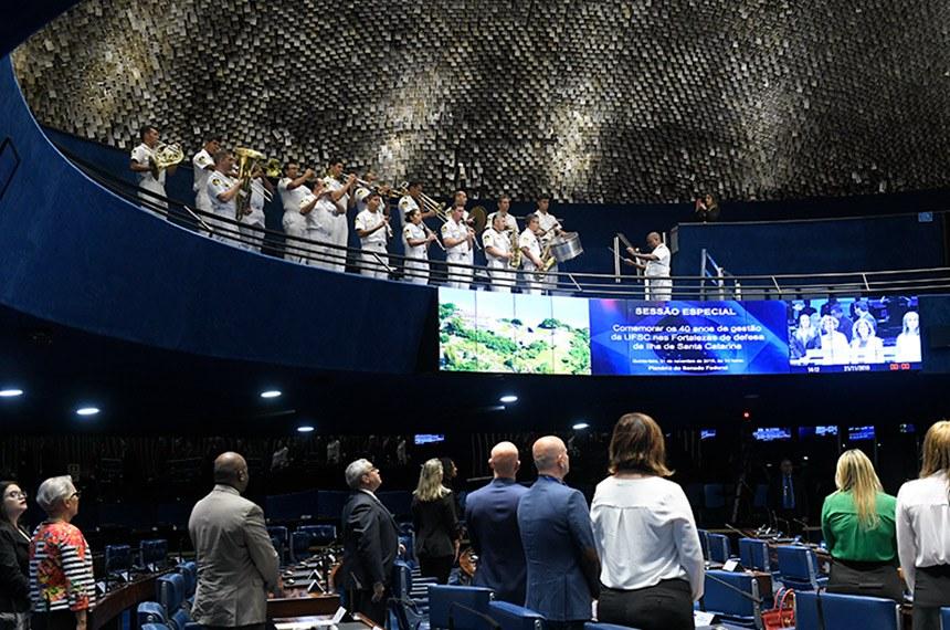 Plenário do Senado Federal durante sessão especial destinada a comemorar os 40 anos de gestão da Universidade Federal de Santa Catarina (UFSC) nas Fortalezas de defesa da Ilha de Santa Catarina.  Em posição de respeito, parlamentares e convidados acompanham execução do Hino Nacional do Brasil executado pela banda de música do Grupamento de Fuzileiros Navais de Brasília.  Mesa: reitor da Universidade Federal de Santa Catarina (UFSC) no período de 1988-1992, Bruno Rodolfo Schelemper Junior; deputada Angela Amin (PP-SC); presidente e requerente desta sessão de comemoração, senador Esperidião Amin (PP-SC); reitor da Universidade Federal de Santa Catarina (UFSC), Ubaldo Cesar Balthazar; presidente do Instituto do Patrimônio Histórico e Artístico Nacional (Iphan), Kátia Santos Bogéa; reitor da Universidade Federal de Santa Catarina (UFSC) no período de 1988-1992, Lúcio Botelho; reitor da Universidade Federal de Santa Catarina (UFSC) no período de 1992-1996, Antônio Diomário de Queiroz.  Foto: Roque de Sá/Agência Senado