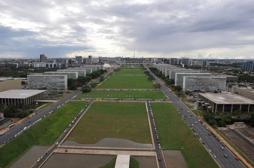 BIE - Banco de imagens externas: Vista aérea da Esplanada dos Ministérios.   Um dos maiores pontos turísticos de Brasília a Esplanada dos Ministérios está localizada no eixo monumental, via que corta o Plano Piloto no sentido leste-oeste, entre os edifícios dos ministérios, que foram projetados pelo arquiteto Oscar Niemeyer. A esplanada é formada por um conjunto de 17 edifícios distribuídos harmoniosamente e com uma regularidade arquitetônica singular. Os edifícios, que ficam em lados opostos no Eixo Monumental, são separados por um grande gramado, onde acontecem shows e eventos, geralmente abertos à população.