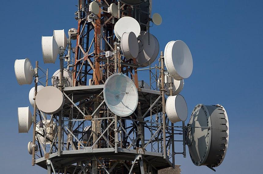 Telecommunication mast, iron tower with group of parabolic antennas.   Mastro de telecomunicações, torre de ferro com grupo de antenas parabólicas.