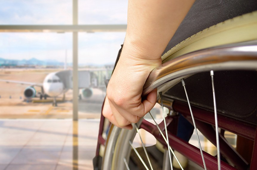 rear view of a woman in wheelchair at the airport with focus on hand ----- Mulher cadeirante na sala de espera de aeroporto