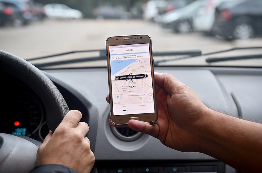 """BIE - 28/06/2016 - Aparelho de celular exibe na tela aplicativo Uber, transporte individual privado.  Projeto de lei do Senado muda as regras para a distribuição do Imposto sobre Serviços (ISS) cobrado no transporte por meio de aplicativos — como Uber, Cabify e 99. De acordo com o PLS 390/2017, o ISS deve ser arrecadado pelo município onde o passageiro iniciou a viagem. Atualmente, o ISS é repassado para a cidade onde o motorista está registrado.  O PLS 390/2017 foi proposto pelo senador Pedro Chaves (PRB-MS). Ele argumenta que o motorista de um serviço de aplicativo pode pegar um passageiro em uma cidade e transportá-lo a outra. Como não tem obrigação de retornar """"vazio"""" ao município de origem, ele pode assumir novas corridas em cidades diferentes daquela onde efetivamente está registrado.  Foto: Ederson Nunes/CMPA"""