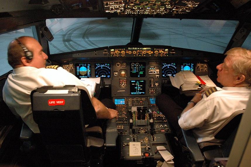 Pilotos no interior da cabine de controle da aeronave.