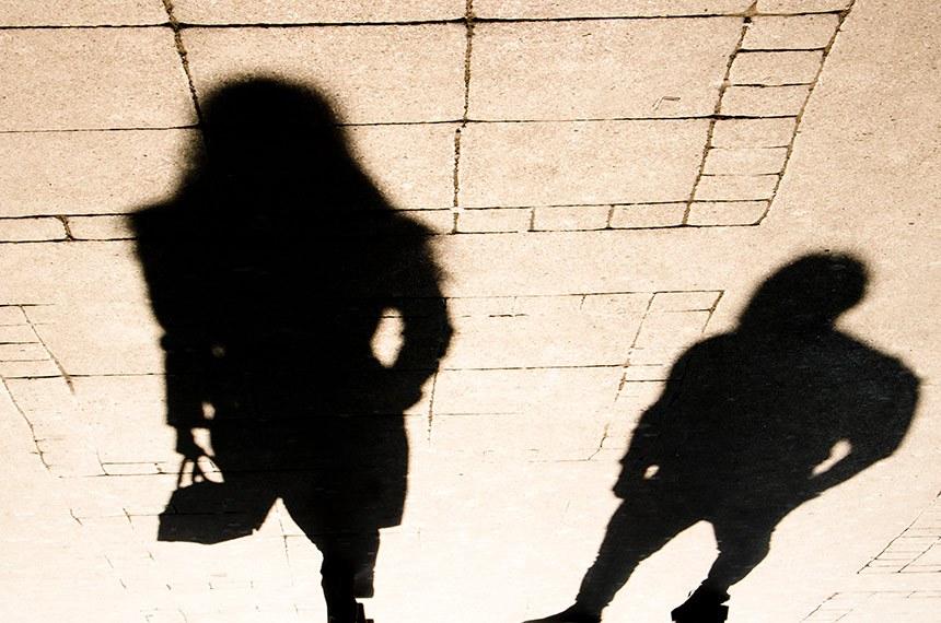 Silhouette shadow of a woman and a man on city sidewalk in sepia black and white.   Assédio moral no trabalho.   Silhueta de mulher e homem na calçada.