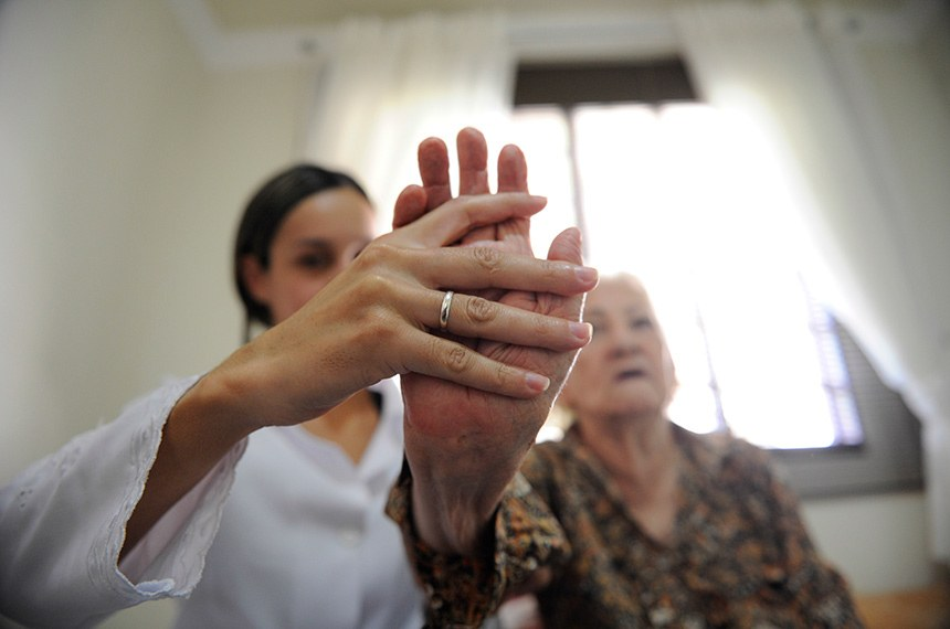 Fisioterapia em casa. Profissionais da saúde cuidam de idosos.