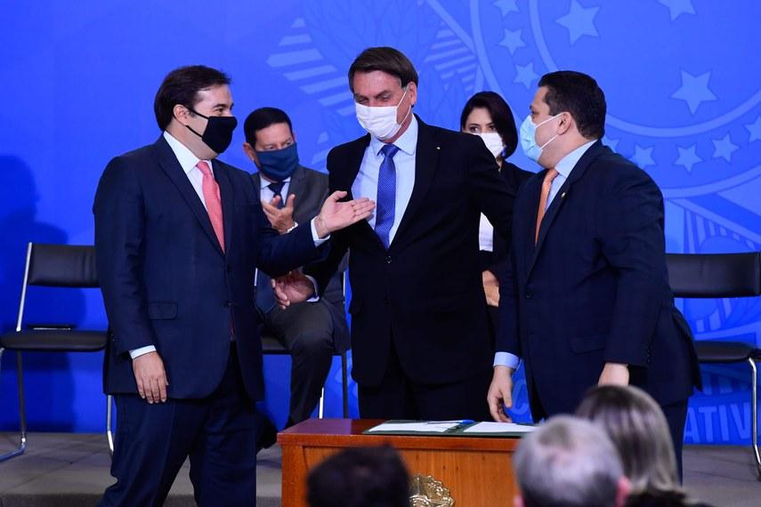 Os presidentes do Senado, Davi Alcolumbre (D), e da Câmara, Rodrigo Maia (E), com o presidente da República, Jair Bolsonaro, que assinou decretou para estender o auxílio