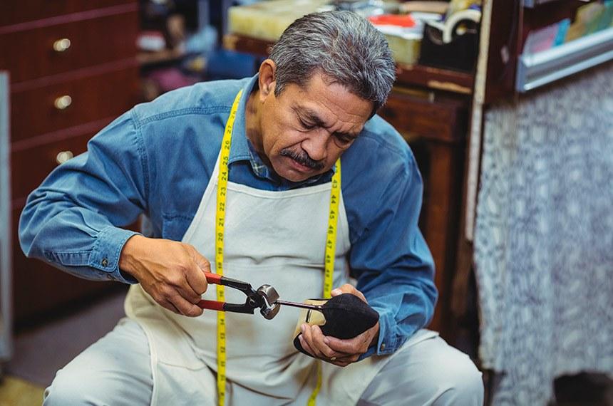 Shoemaker hammering on a shoe  -----  Fabricante de sapatos. Idoso trabalhando
