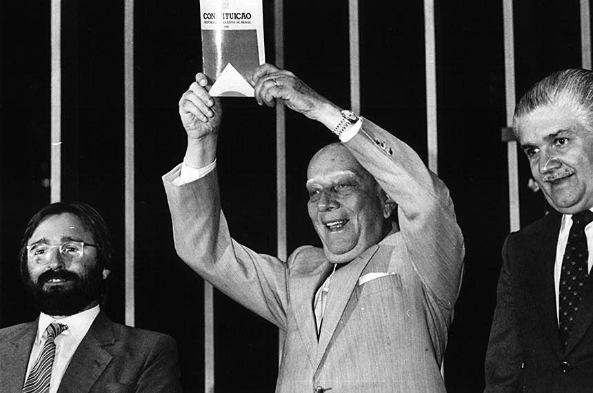 BIE - 03/10/1988 - Plenário da Câmara dos Deputados durante sessão plenária da Assembleia Nacional Constituinte - Votação de Matérias.  A Assembleia Nacional Constituinte completa 30 anos de instalação. Na foto, o presidente da Assembleia, deputado Ulysses Guimarães, no dia da promulgação do texto na assembleia   O presidente da Assembléia Nacional Constituinte, deputado Ulysses Guimarães (PMDB-SP), ergue o primeiro exemplar da Constituição de 1988.  Mesa:  2º vice-presidente da Assembléia  Nacional Constituinte, deputado Marcelo Cordeiro (PMDB-BA); presidente da Assembléia Nacional Constituinte, deputado Ulysses Guimarães (PMDB-SP); 1º vice-presidente da Assembléia Nacional Constituinte, deputado Mauro Benevides (PMDB-CE).  Foto: Acervo SEDI/CD