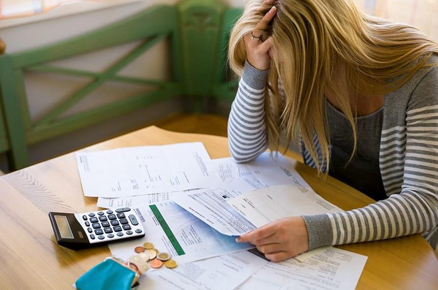 Mulher contrariada, triste, faz calculos com pilha de contas