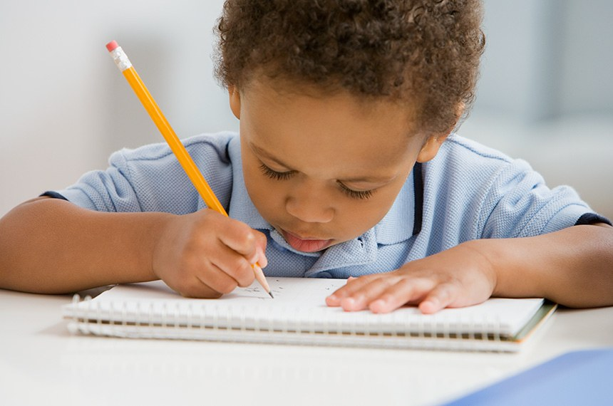 African boy drawing on notebook