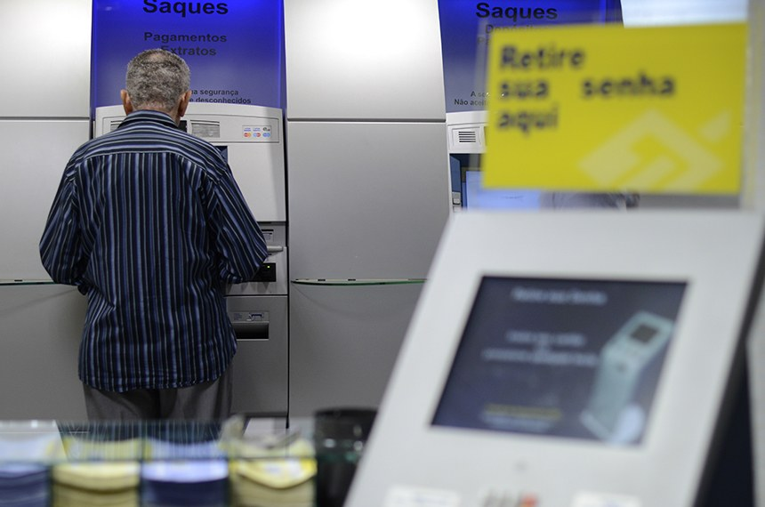 Idosos utilizam terminais de auto atendimento em banco público.