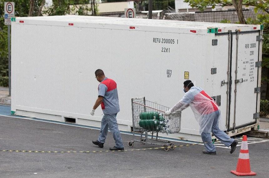 Funcionários transportam cilindros ao lado de câmara frigorífica de corpos. Manaus enfrenta o caos na saúde com a alta de casos na segunda onda de Covid-19. Falta de suplementos hospitalares como oxigênio têm contribuído para o aumento do número de mortos. (Foto: Bruno Kelly/Amazônia Real)