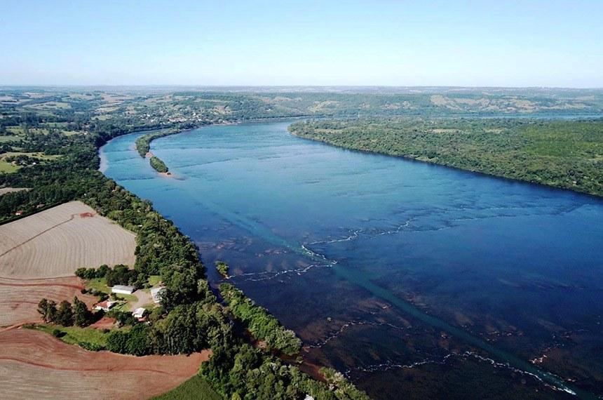O rio Uruguai, em Porto Mauá,está com o nível das suas águas bem baixo e transparentes.  O rio Uruguai, em Porto Mauá, principalmente na localidade de Volta Grande, distante em torno de 8 km da cidade, está com o nível das suas águas bem baixo e transparentes.  Olhando-se do alto, é possível ver nitidamente onde cruza o canalão (largura 10 a 15m e profundida 25 a 30m) e as pedras no fundo do seu leito, sendo que as pedras estão começando a ficar emersas, mas nada comparável ao que ocorreu no dia 24 de maio de 2012, quando era possível atravessar a pé, em sentido transversal (oblíquo) o rio Uruguai até à Argentina, numa distância aproximada de 1.000 metros, sendo que em linha reta a distância é de 770m, bastava apenas cruzar o canal com um caíco.  Algumas secas: 2012, 2005, 1979 (2ª maior) e 1942 (maior seca com 6 meses sem chuva).  As imagens e o baixo nível do rio Uruguai, mostram o percurso realizado pelo canalão, sendo que na segunda e terceira ilha, cruza ao lado de ambas, entre um e dois metros de distância, em alguns lugares passa a menos de dois metros do barranco do rio, sendo um perigo para quem frequenta estas duas ilhas e a própria costa do rio. O baixo nível também revela as pedras e o perigo que elas representam para as embarcações que frequentam o rio, por estes motivos, é indispensável o uso de coletes salva vidas aos que frequentam o rio.  Na localidade de Três Pedras, interior de Novo Machado, basta passar o canalão, que é possível atravessar o rio Uruguai a pé, caminhando sobre as pedras emersas do rio Uruguai, num percurso de apenas 500 metros de distância.  Texto: Vilson Winkler Foto: Silvio da Silva Vargas